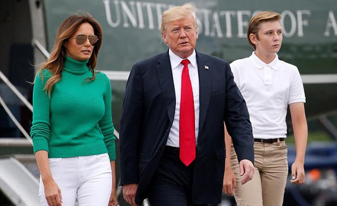 Barron mặc áo sơ mi trắng kết hợp quần kaki và giày thể thao. Cậu bé trông bảnh bảo khibước đi sau lưng bố.
