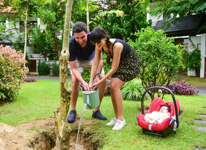 Vờ chồng Hà Anh vừa chăm con vừa tranh thủ trồng cây trong vườn nhà.