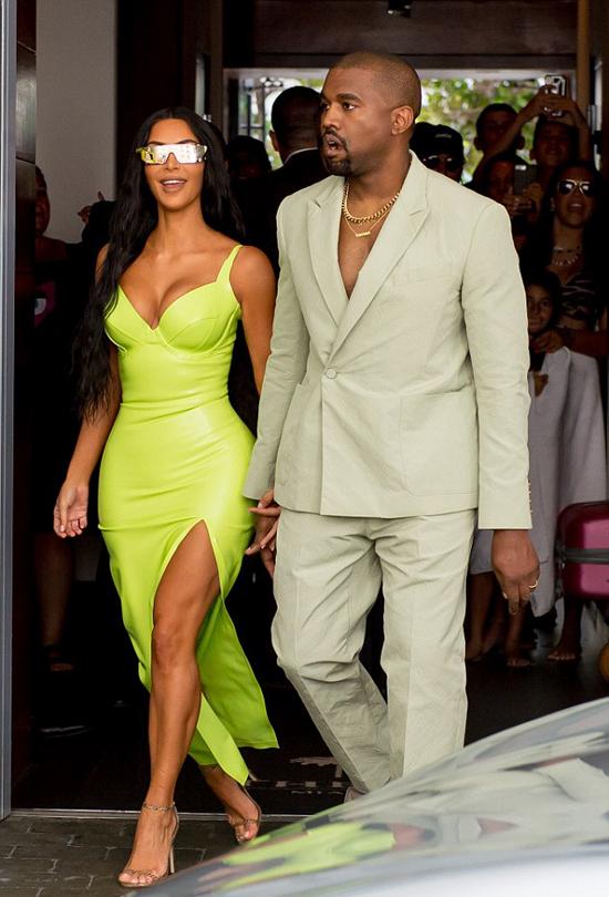 Kim nổi bật với bộ đầm màu neon bó sát trong khi Kanye diện vest phóng khoáng của Louis Vuitton và xỏ dép thương hiệu Yeezy của chính anh.