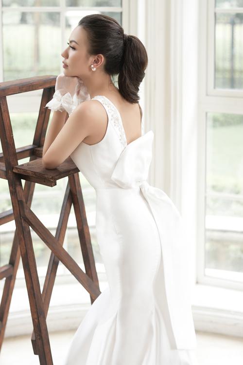 Đằng sau váy là khoảng cut outgiúp cô dâu khoe khéolàn da mịn màng, không tì vết. Nơ to bản được đính ngang eo khiến cô dâu trông thật ngọt ngào và trẻ trung.