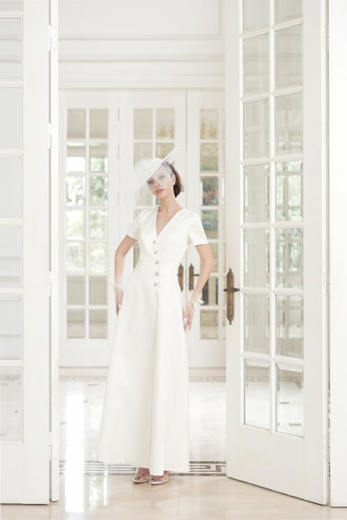 Váy cưới chữ A thêm thanh lịch với hàng cúc được đínhtừ ngực xuống tới eo. Thiết kế cổ chữ V xẻ ngựckhông quá sâu mang đến vẻ đẹp cổ điển, kín đáo cho bất kì cô gái nào khoác lên mình chiếc váy cưới này.