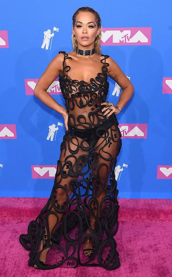Ca sĩ người Anh, Rita Ora khoe dáng trên thảm đỏ MTV Video Music Awards 2018 trong bộ đầm Paul Gaultier xuyên thấu. Năm nay, cô được đề cử giải Video nhạc dance xuất sắc với ca khúc Lonely Together kết hợp cùng DJ quá cố Avicii.
