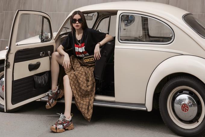 Với mẫu giày của Gucci, cô chọn áo thun in họa tiết chữ size lớn, đi cùng chân váy midi có họa tiết bắt màu. Mốt túi đeo ngang hông cũng được cô áp dụng cho ngoại hình.