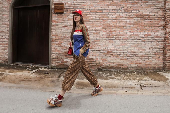 Nón và túi đeo Gucci có màu đỏ đồng điệu trở thành điểm nhấn khi người đẹpxuống phố.