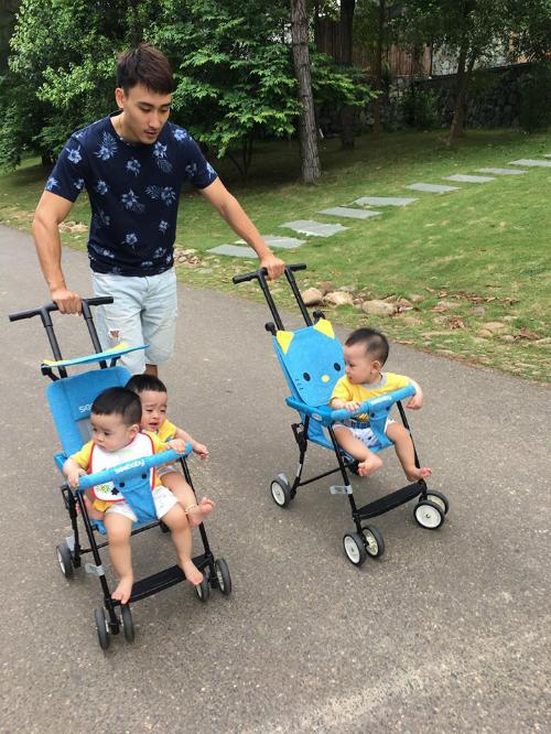 Anh Trung đẩy 3 con đi dạo.