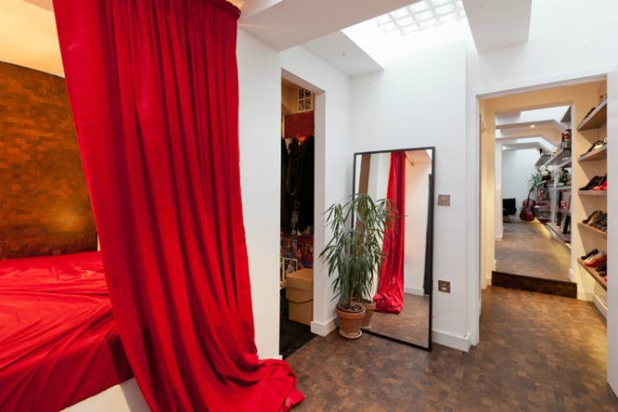 Điểm nhấn của căn hộ này là phòng ngủ kết hợp hai màu sắc đỏ và vàng. Nội thất phòng ngủ gồm chiếc giường có màn che và chiếc gương kích thước lớn.