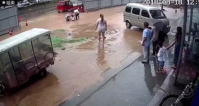 Người dân hợp sức giải cứu hai bé gái bị thụt xuống hố. Ảnh: AsiaWire.