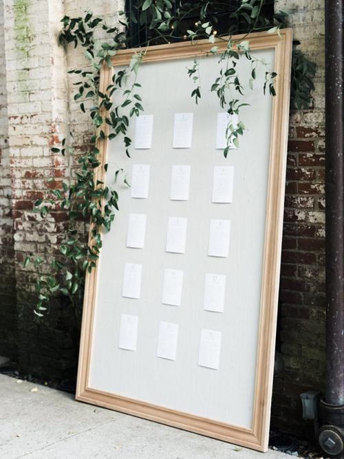 Tấm bảng thông báo vị trí bàn tiệckhông có họa tiết trang trí mà chỉ cótờ danh sách chỗ ngồi được dán lêntrên. Uyên ương gắnvài nhành lá có tông xanh (Greenery)để tấm bảng bớt đơn điệu.