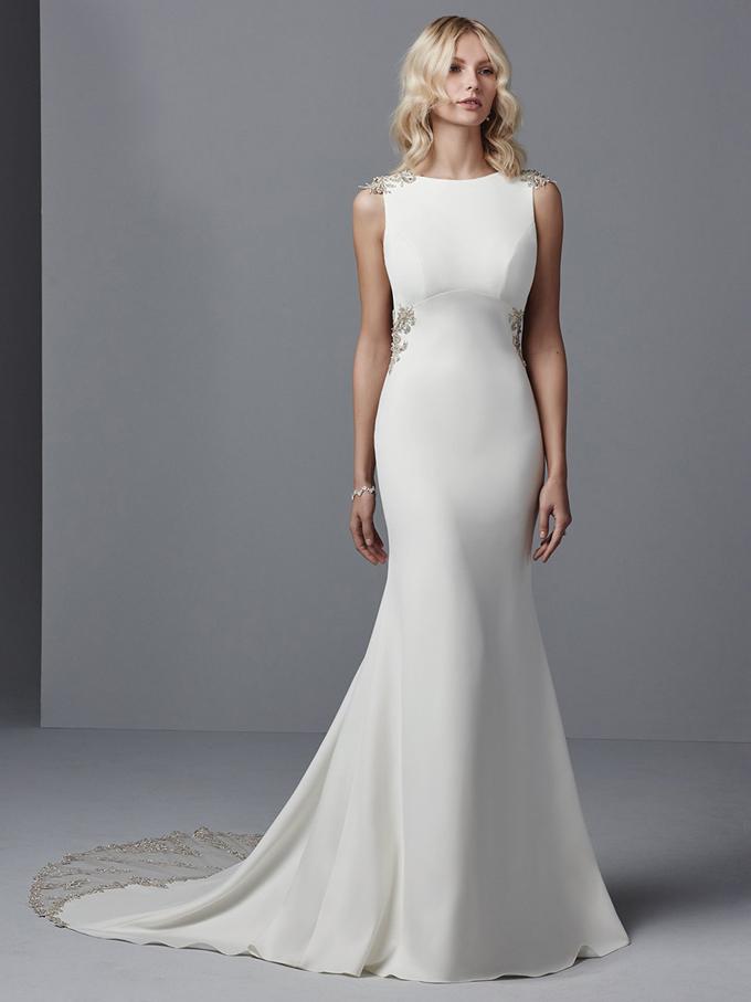Chiếc váy dáng Sheath có giá 2.538 USD được đính pha lê Swarovski ở cầu vai và ngang hông.Điểm nổi bật ở thiết kế cưới là phom dáng cân bằng tới độ tuyệt hảo. Tà váy được đính voan và pha lê Swarovskikhông quá dài giúp cô dâu dễ dàng di chuyển.