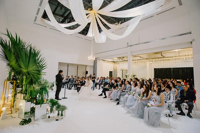 Toàn cảnh của lễ đường mang tôngtrắng tinh khôi. Không gian bớt tẻ nhạt nhờ những dải lụa trắng, đèn treo và đèn chùm do wedding planner bố trí.