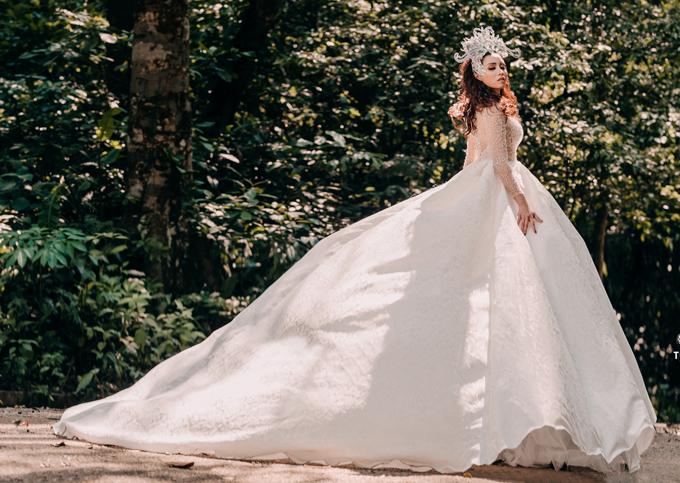 Váy cưới phom công chúa với phần đuôi dài và tùng váy gồm nhiều lớp vải lưới tạo độ phồng, nhẹ.