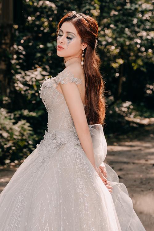 Chiếc váy bắt sáng nhờ chất liệu lụa dệt kim tuyến. Hoa văn 3D điể xuyết tạo điểm nhấn điệu đà.