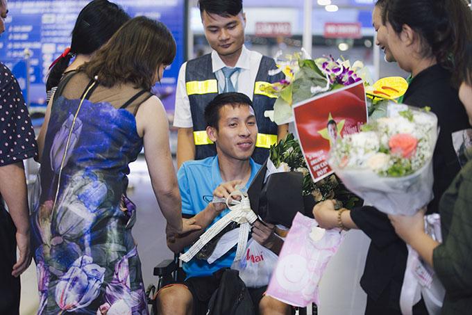 Hùng Dũng vui vì được nhiều người ra đón, tặng hoa và hỏi thăm sức khỏe.