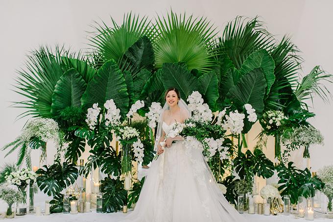 Loài hoa chủ đạo của hôn lễ là lan hồ điệp và hồng trắng. Cô dâu chọn khá nhiều loại lá đến từ rừng nhiệt đới như lá cọ, lá cây monstera deliciosa với thùy lá dạng lông chim để tạo điểm nhấn cho không gian. Tất cả các chi tiết trang trí ở lễ đường đều được tái sử dụng trong tiệc cưới.
