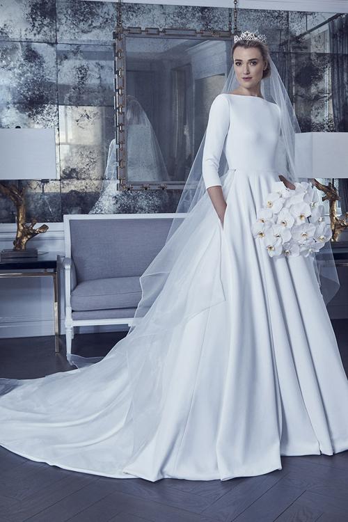 Trong bộ sưu tập mùa xuân năm 2019 của Romona Keveza, váy cưới được may bằng vải lụa crepe trơn và có dáng cổ thuyền. Đặc trưng của lụa crepe là bề mặt bóng, mịn, không dễ nhăn như các loại vải khác và mang đến cho người dùng cảm giác nhẹ nhàng. Nhà thiết kế còn đínhtà phụ ngang hông để tạo điểm khác biệt cho chiếc váy.