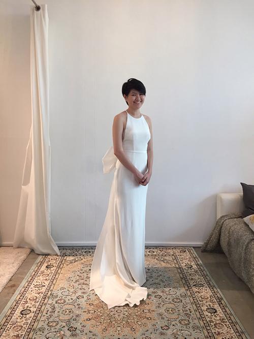 Váy cưới tối giản được may từ lụa và có thêm tà phụ đằng sau. Bộ váy thêm phần nữ tính nhờ thiết kế cổ yếm.