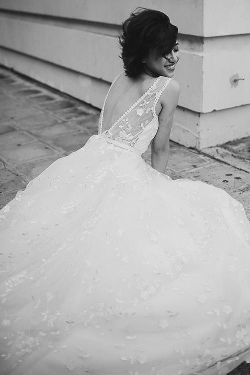Chiếc váy được thổi làn gió của sự tự do thông qua khoảng hở tinh tế ở lưng và lớp voan mỏng thêu họa tiết hoa nổi.