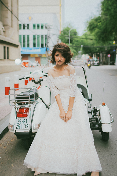 Chiếc váy ren chữ A dường như sinh ra để dành ra cho mọi nàng dâu. Thiết kế có cổ hai trong một (cổ voan mờ và trễ vai), nhiều tầng lớp bên trong váy để mỗi bước đi của cô dâu thướt tha, uyển chuyển hơn.