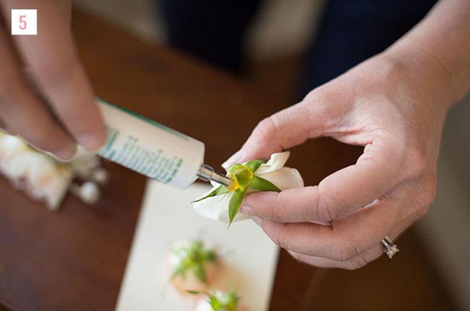 Bước 5: Bạn tiếp tục dùng keo dán vào cuống hoa và đính hoa lên lược cài.Dùng tay để ấn, cố định hoa trên lược từ 15-20 giây.