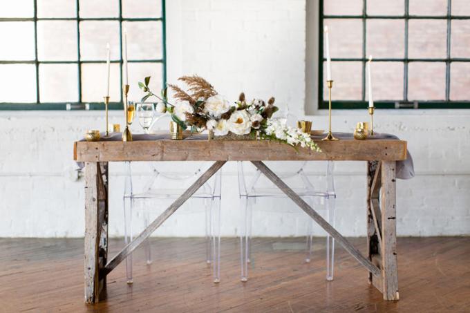 Nội thất bằng gỗ và ghế ngồi trong suốt: Thông thường, bàn tiệc dành cho uyên ương thương có các chi tiết trang trí sang trọng và phức tạp, tuy nhiên bàn tiệc trongđám cưới tối giản có một chút khác biệt. Trong tấm ảnh này, chiếc bàn uyên ương được làm bằng gỗ và có thêmgiá nến kim loại, cốc kim loại màu vàng đồng.