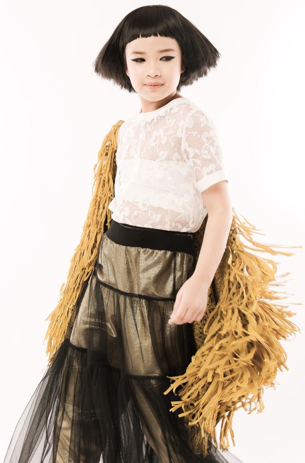 Áo khoác thua rua được chọn lựa làm điểm nhấn nổi bật trên set đồ gồm áo ren trắng mỏng và chân váy xếp tầng.