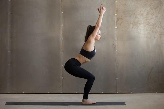 Tư thế chiếc ghế (Chair pose)Đứng trên sàn nhà hoặc thảm, uốn cong cả hai đầu gối cùng một lúc với tư thế như đang ngồi. Hai tay giơ cao, đặt sát vào hai bên tai, lòng bàn tay hướng vào nhau. Giữ vai, lưng thẳng trong 5 lượt thở rồi trở về vị trí ban đầu. Lặp lại từ 5-10 lần.Đây là động tác giảm mỡ bụng và hông, săn chắc cơ chân, bắp tay.