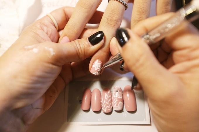 Màu hồng được phối kết với nét vẽ hoa màu trắng. Bạn gái có thể chọn hai ngón tay bất kỳ để yêu cầu vẽ và đính đá.