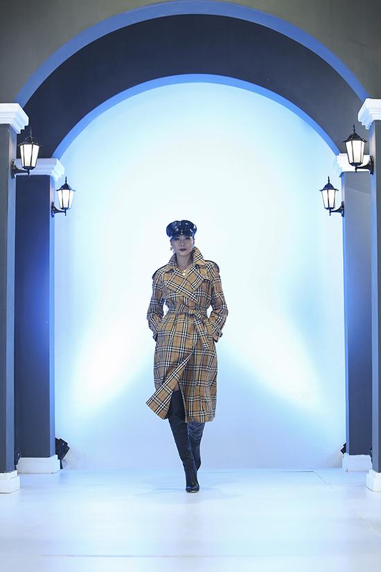 Thanh Hằng lựa chọn set đồ theo phong cách mùa đông với áo măng tô burberry, bốt da cao cổ tiệp màu mũ da bóng.