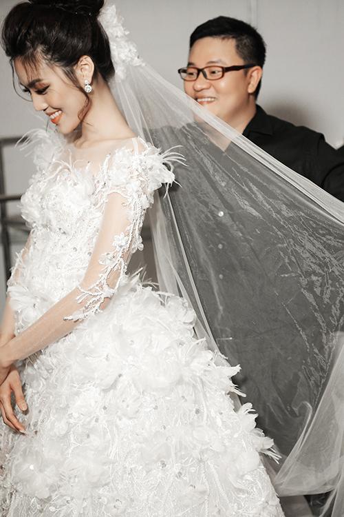 Để hoàn thiện chiếc váy, NTK Vĩnh Thụy và 5 người thợ thêu lành nghề đã miệt mài đính kết lông vũ, cánh hoa trong vòng một tháng liên tục.