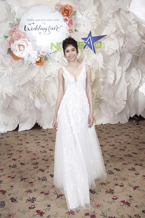 Người mẫu diện váy có cổ chữ V xẻ sâu nhưng có dải voan mỏng để tiết chế khoảng hở. Dải họa tiết chạy dọc thân váy tạo sự uyển chuyển, mềm mại.