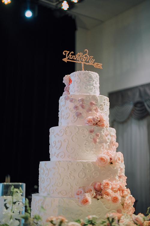 Bánh cưới 5 tầng của uyên ương được điểm xuyết bởi họa tiết hoa văn cổ điển và những bông hồng phớt.