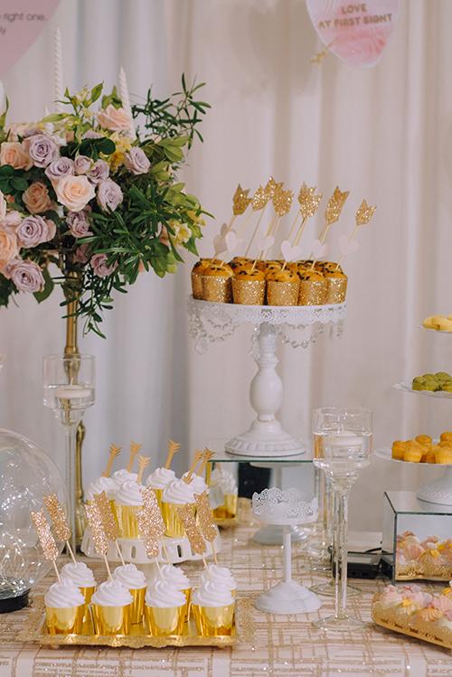 Rất nhiều chiếc bánh cupcake và bánh bông lan xinh xắn được bố trí ở bàn tiếp tân. Tất cả đều được tô điểm bởi hình ảnh mũi tên tình yêu.