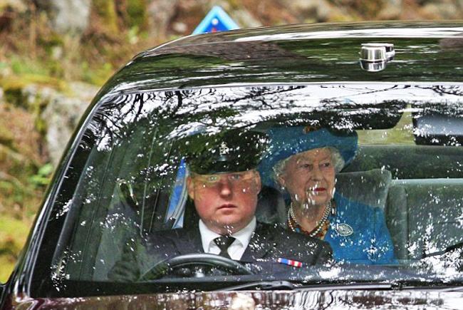 Trái ngược với cháu dâu, Nữ hoàng vẫn ưa chuộng trang phục có màu sắc tươi sáng. Bà mặc áo khoác màu xanh, bên trong là váy hoa kết hợp hai màu xanh và cam đậm. Nữ hoàng kết hợp trang phục với chiếc mũ ton sur ton và đeo một chiếc vòng cổ cũng bằng ngọc trai.