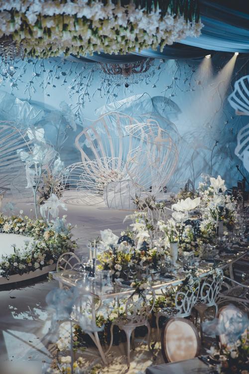 Tông màu chủ đạo của hôn lễ là xanh nhạt và trắng. Cặp vợ chồng sử dụng rất nhiều hoa trắng để trang trí vàchọn ghế, bàn tiệc theo phong cách châu Âu cổ điển.