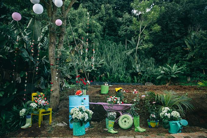 Gia đình của cô dâu đã có sẵn những dụng cụ làm vườn nên uyên ương đã tận dụng những đồ vật này để trang trí. Cả hai tân trang lại chúng bằng cách sơn màu sặc sỡ và cắm hoa để không gian thêm sinh động. Theo uyên ương, việc tự trang trí cho lễ vu quy và lễ thành hôn giúp cả hai tiết kiệm chi phí từ 4-5 lần so với việc đi thuê.