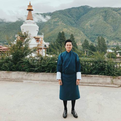 Hoàng tử sơn ca Quang Vinh diện trang phục truyền thống của vương quốc Bhutan. Nam ca sĩ tiết lộngười dân nơi đây sẽ mặc đồ này đi làm, đi học.