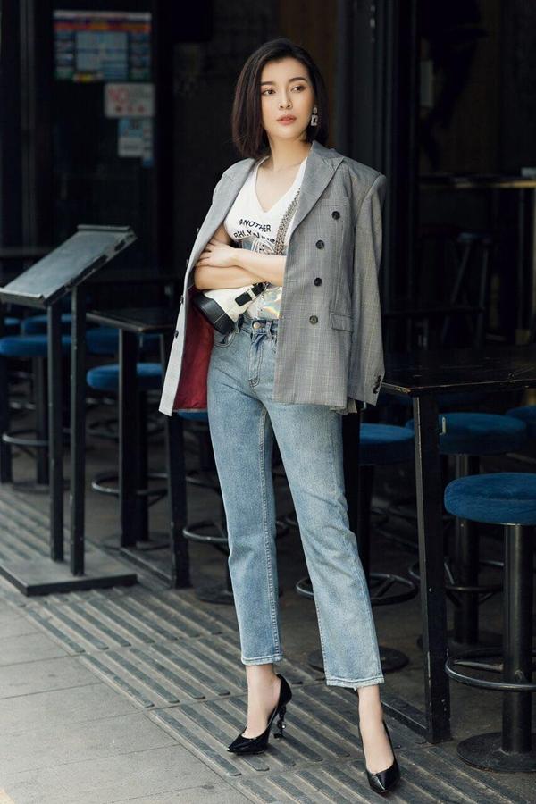 Cao Thái Hà kết hợp áo blazer với áo thun trắng, quần Jean ống rộng giúp cô thoải mái xuống phố. Túi Chanel Gabrielle và đôi giày YSL là hai món hàng hiệu hoàn thiệnset đồ của nữ diễn viên.