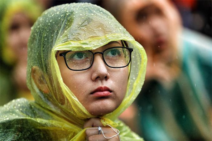 Gương mặt ướt nước mưa nhưng cô gái vẫn chăm chú hướng mắt lên màn hình.