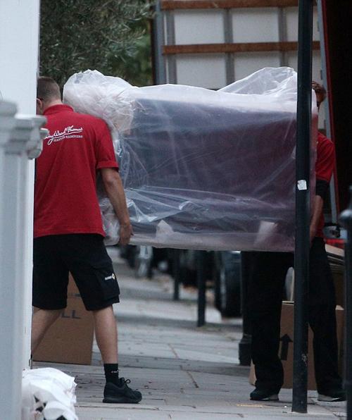 Giường, đệm, bàn ghế, đồ dùng nhà bếp được các nhân viên vận chuyển cận thận mang vào trong ngôi nhà.