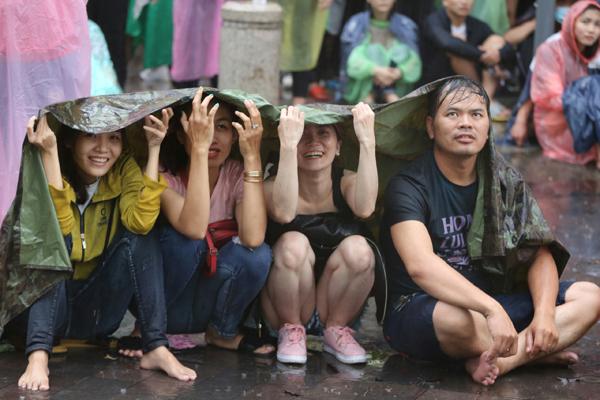 Nhóm thiếu nữ bất chấp mưa lớn, che chung chiếc áo mưa để cổ vũ cho đội nhà.