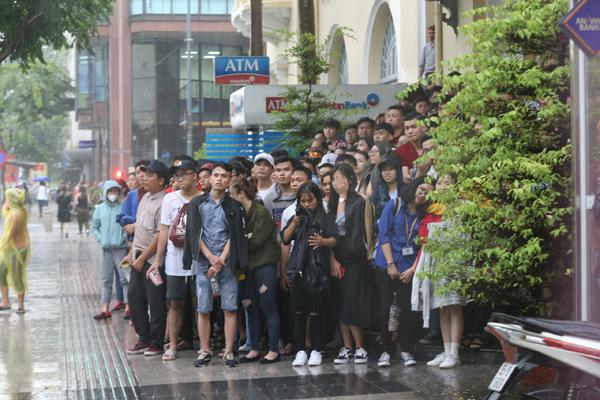 Một số người khác trú mưa ở các sảnh khách sạn trên đường Nguyễn Huệ nhưng vẫn hướng mắt về phía các màn hình để ngóng tình hình trận đấu.