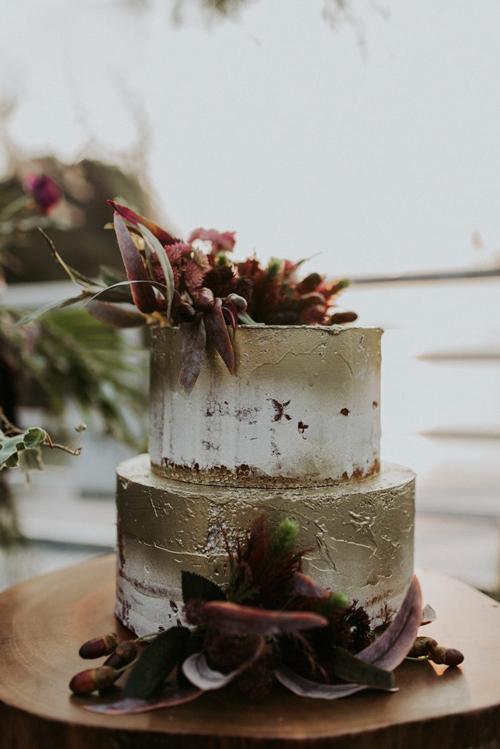 Bánh cưới naked-cake hai tầng được phết rất ít kem xung quanh và được tô điểm bởi hoa tươi đỏ tía.