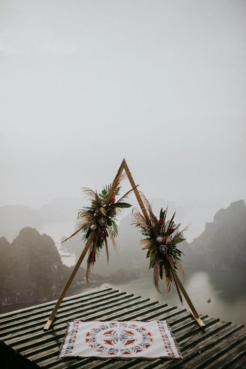 Ekip decor đã dựng sẵn cổng vòm hình tam giác với hoa tươi và tấm thảm có họa tiết boho để uyên ương làm lễ.