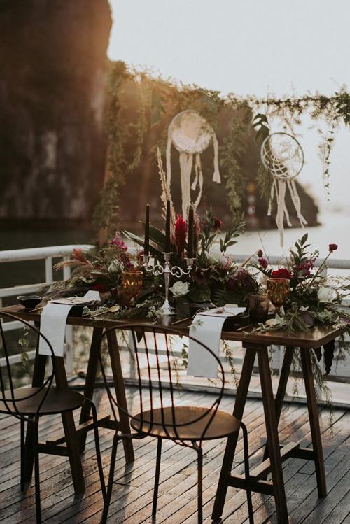 Wedding planner đã thiết kế bàn tiệc mang âm hưởng boho đậm nét với những chiếc dreamcatcher, hoa cỏ sậm màu và giá nến.