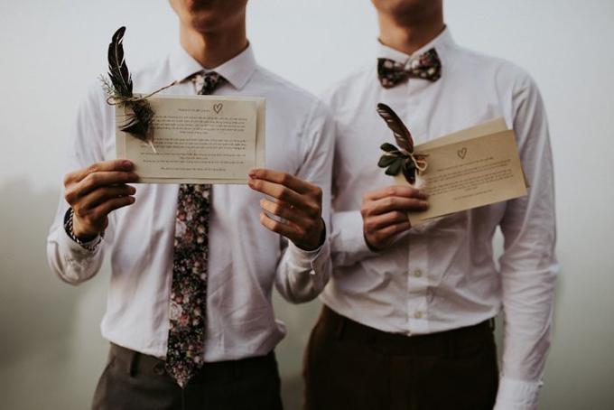 Tấm thiệp cưới được uyên ương nâng niu và điểm xuyết bởi những cánh lông vũ. Cả hai chọn phụ kiệnlà nơ và cà vạt có cùng họa tiết.