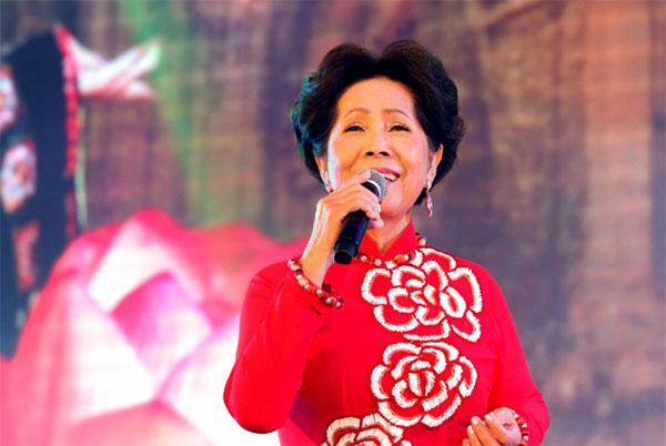 Danh ca Phương Dung diện áo dài đỏ khi xuất hiện trên sân khấu.
