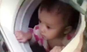 Bé 1 tuổi ngồi trong máy giặt để thoát khỏi ngôi nhà ngập nước