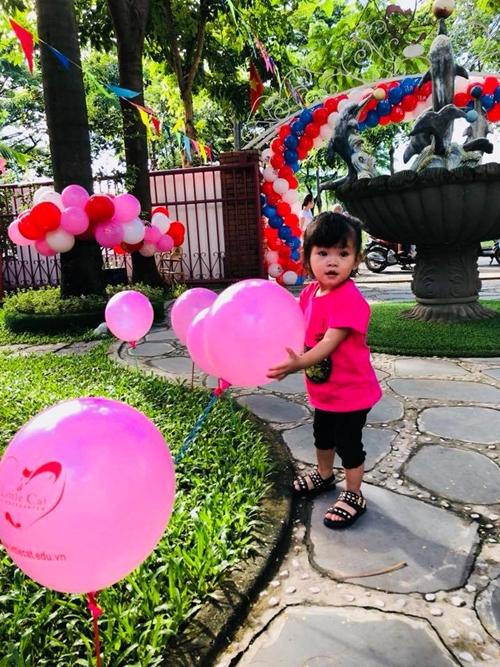 Bé Kem nhà Hải Băng thích thú với những chùm bóng bay nhiều màu sắc.