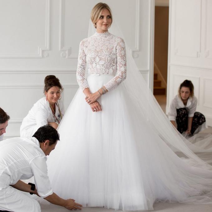 Bộ váy đầu tiên mà Chiara diện trong buổi lễ chính là một thiết kế mang phom dáng truyền thống.Nhiều người trong làng thời trang cho rằng chiếc váy của cô gợi nhắc đến hai chiếc soiree của Công nương Kate Middleton và Công nương Grace Keally bởi chi tiết ren cao cấp ở tay và cổ áo. Những người thợ lành nghề của Dior đã tốn 1600 giờ và 400 mét vải để hoàn thành chiếc váy cưới đẹp dịu dàng của Chiara.Ảnh: Dior