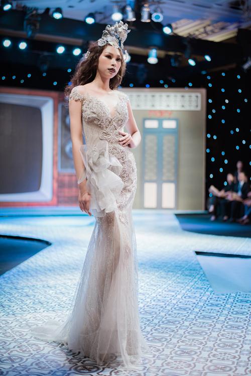 Ren, pha lê lấp lánh được đính từ cầu vai chạy dọc đến gần đầu gối khiến cô dâu thêm nổi bật, lộng lẫy. Chân váy có độ xòe không quá kịch tính, được tạo từ nhiều lớp voan mỏng tạo sự thướt tha khi di chuyển. Hoa 3D từ voan mỏng được đính ngang hông tạo điểm nhấn cho trang phục.
